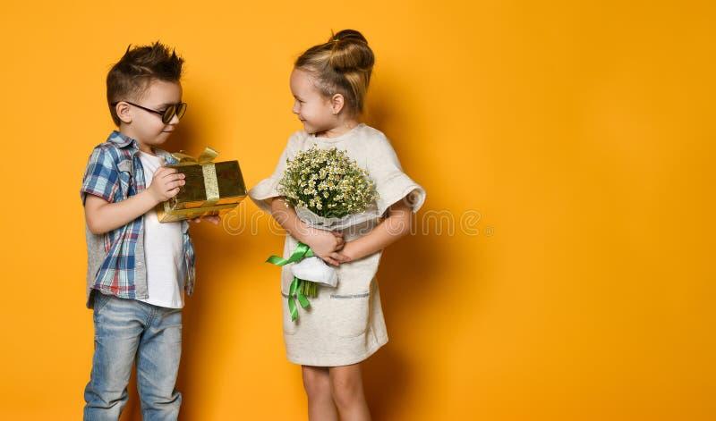 Retrato integral de un hombre sonriente que da una actual caja a su novia sobre la pared gris imagen de archivo libre de regalías