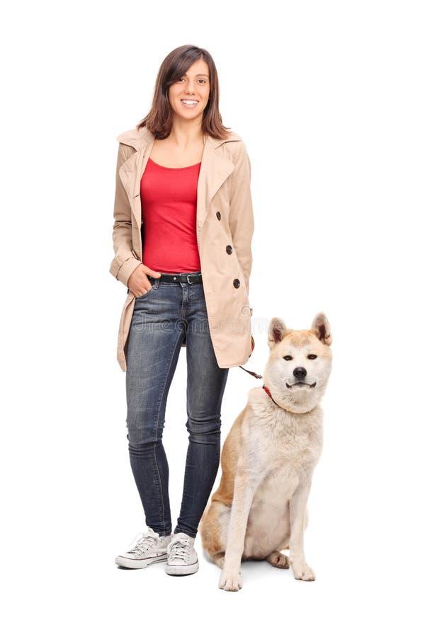 Retrato integral de una chica joven que presenta con el perro foto de archivo libre de regalías