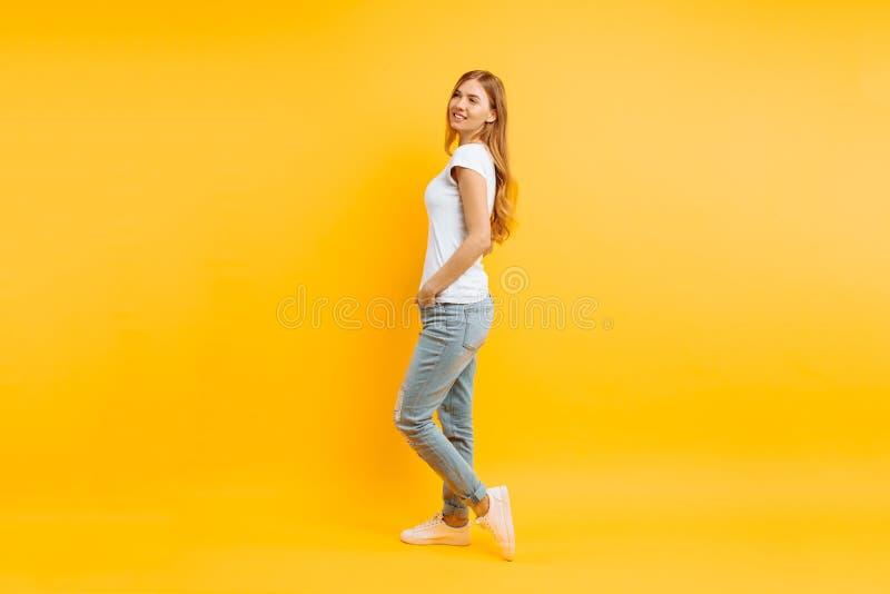 Retrato integral de una muchacha hermosa alegre, presentando en un fondo amarillo imagenes de archivo