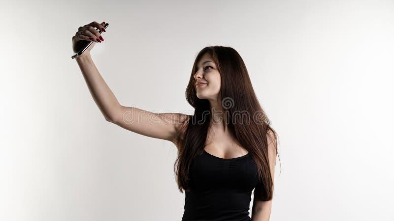 Retrato integral de una mujer bonita joven alegre que hace el selfie usando el teléfono móvil sobre el fondo blanco foto de archivo libre de regalías