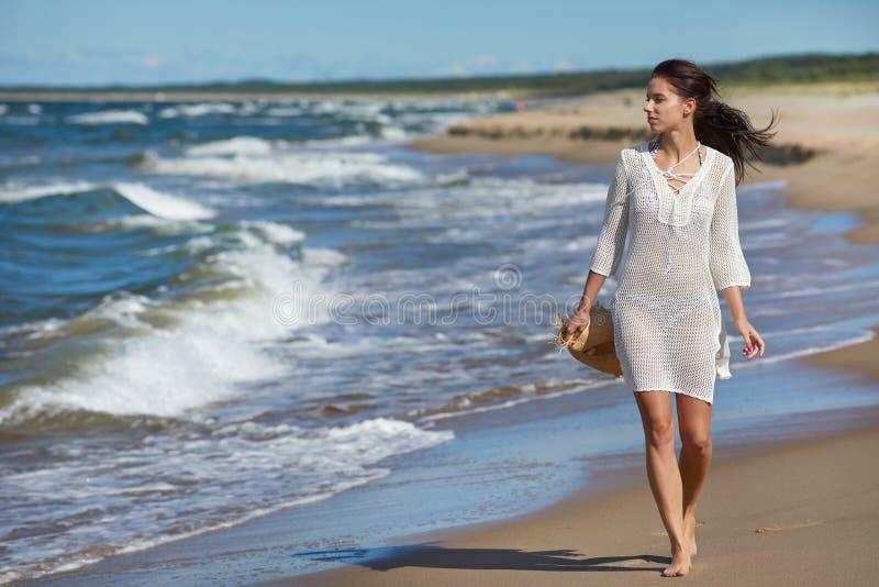 Retrato integral de una mujer joven en pantalones cortos que camina en el b fotografía de archivo libre de regalías