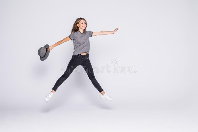 Retrato integral de una mujer linda alegre que salta con el sombrero aislado en un fondo blanco imagen de archivo libre de regalías