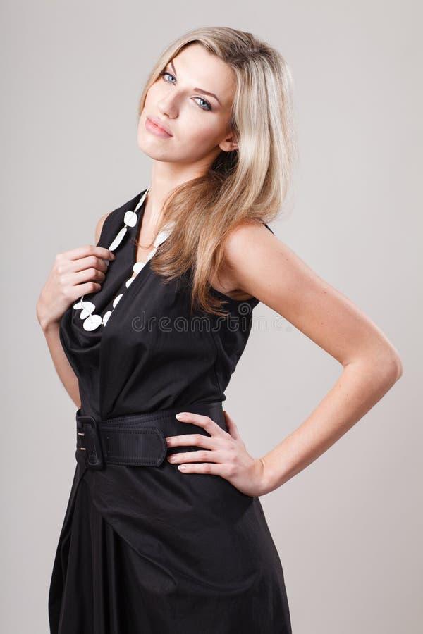 Retrato integral de una mujer rubia atractiva en poco vestido negro de la moda foto de archivo libre de regalías