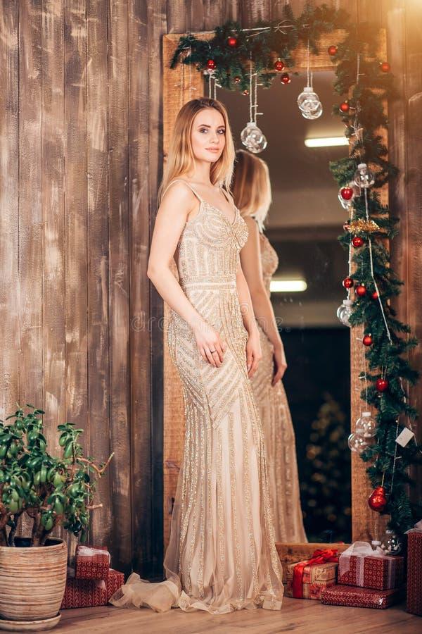 Retrato integral de una mujer rubia elegante en un vestido de oro largo cerca del espejo adornado con las ramas de la Navidad y fotos de archivo