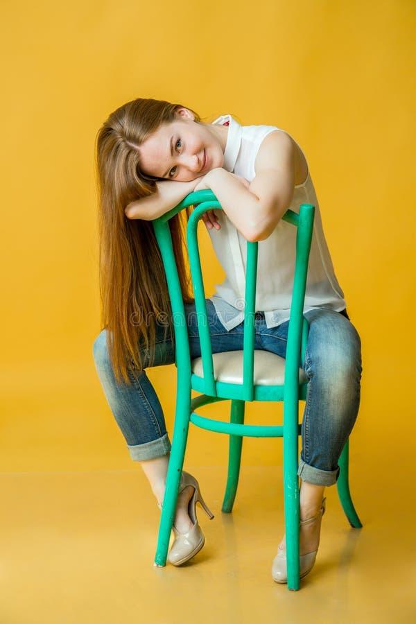 Retrato integral de una sentada linda sonriente de la mujer imagen de archivo libre de regalías