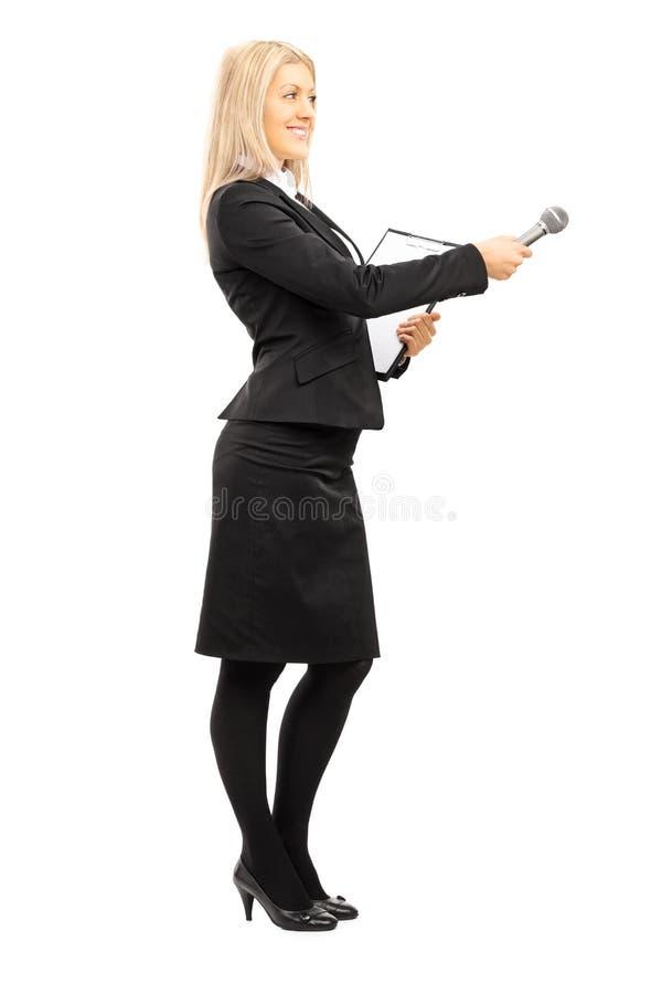 Retrato integral del entrevistador de sexo femenino joven que sostiene un micrófono fotos de archivo