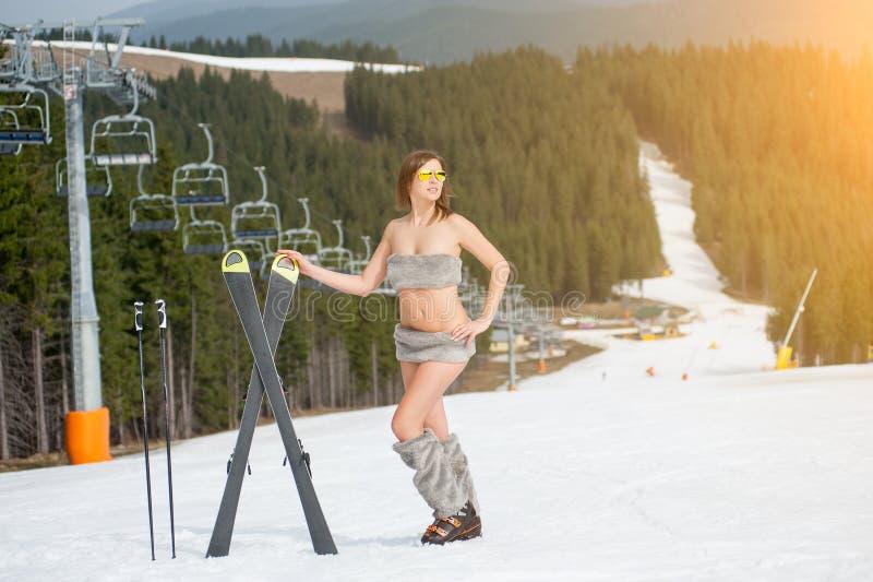 Retrato integral del esquiador de sexo femenino desnudo feliz con los esquís La mujer hermosa está presentando en cuesta nevosa imagen de archivo
