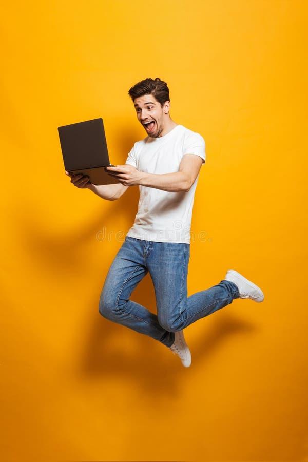 Retrato integral del hombre feliz con el pelo marrón que salta y ho imagen de archivo