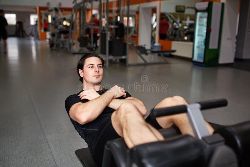 Retrato integral del hombre muscular de la estructura mientras que hace empuje hacia arriba el ejercicio en centro de aptitud fotografía de archivo