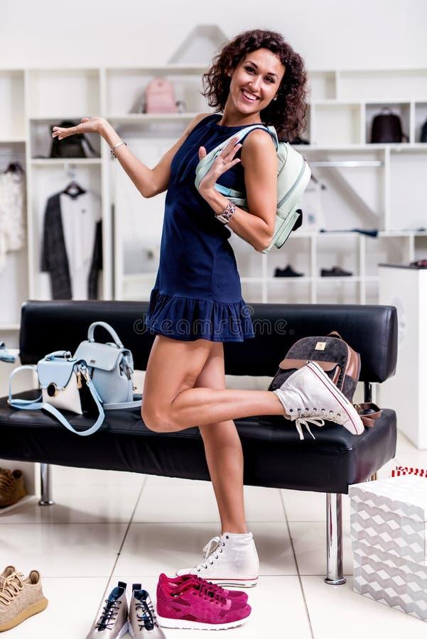 Retrato integral del modelo femenino bastante sonriente que presenta con sus compras que demuestran su nueva mirada en de moda foto de archivo libre de regalías