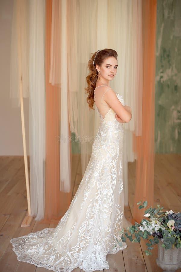 Retrato integral del modelo femenino lujoso hermoso con el pelo marrón medio en un vestido blanco largo en el cuarto imagenes de archivo
