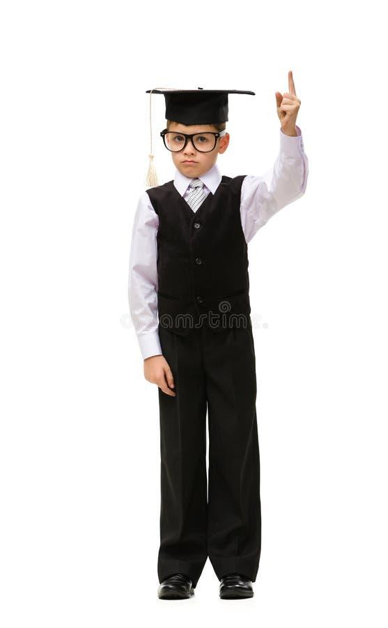 Retrato integral del pequeño estudiante en casquillo académico foto de archivo libre de regalías