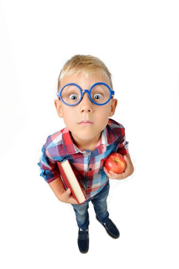 Retrato integral granangular del muchacho un estudiante en camisa en los vidrios que abrazan el libro y la manzana en manos, mira fotos de archivo libres de regalías