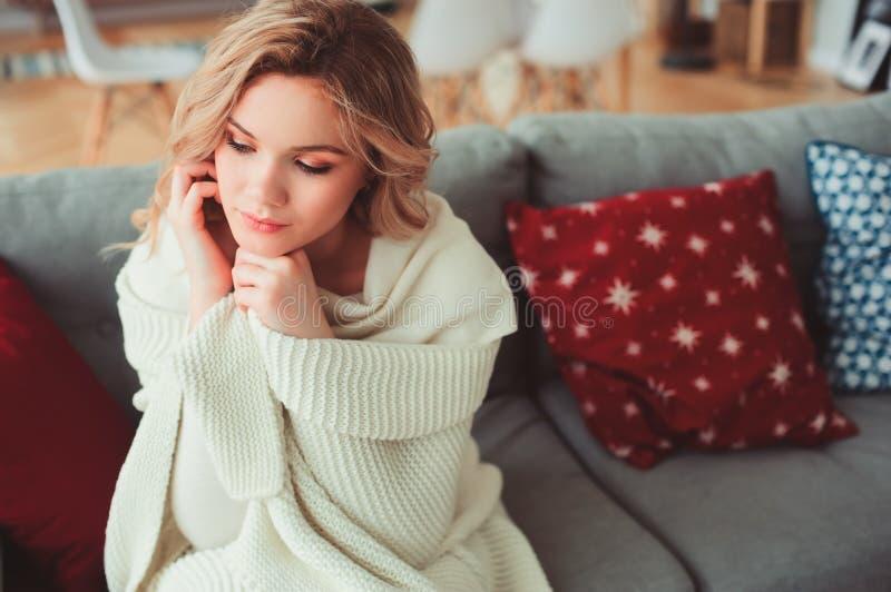 Retrato interior de la mujer hermosa egoísta joven que disfruta invierno en casa, sentándose en el sofá acogedor en suéter calien foto de archivo