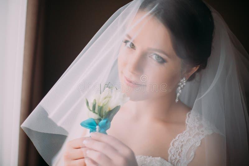 Retrato interior de la novia sensual, muy hermosa en el velo, sosteniendo pequeño boutonniere lindo, primer fotos de archivo libres de regalías