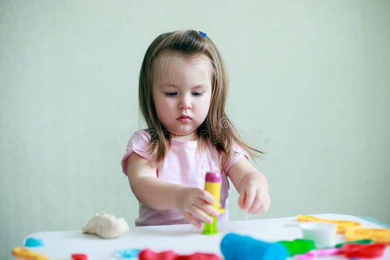 Retrato interior de los 2 años jovenes de muchacha caucásica sonriente feliz del niño que juega con pasta del juego imágenes de archivo libres de regalías