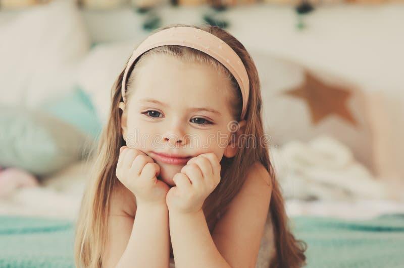 retrato interior de los 5 años lindos tristes de la muchacha del niño que se sienta en cama imágenes de archivo libres de regalías