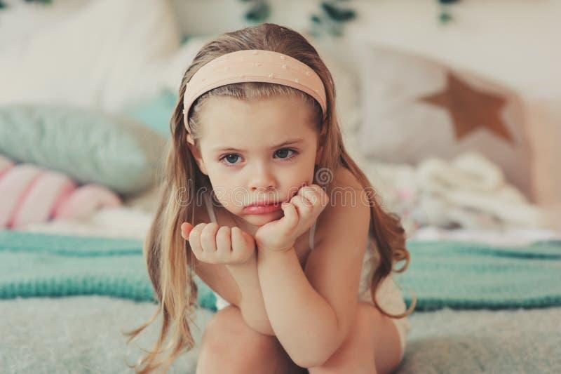 retrato interior de los 5 años lindos tristes de la muchacha del niño que se sienta en cama fotografía de archivo