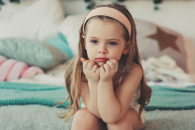 retrato interior de los 5 años lindos tristes de la muchacha del niño que se sienta en cama fotos de archivo