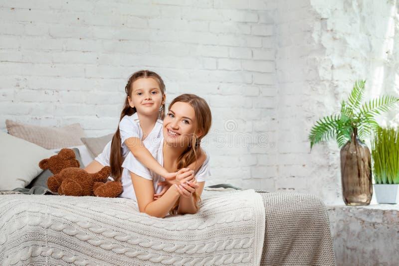 Retrato interior de una madre hermosa con ella pequeña hija encantadora que presenta contra interior del dormitorio fotografía de archivo libre de regalías