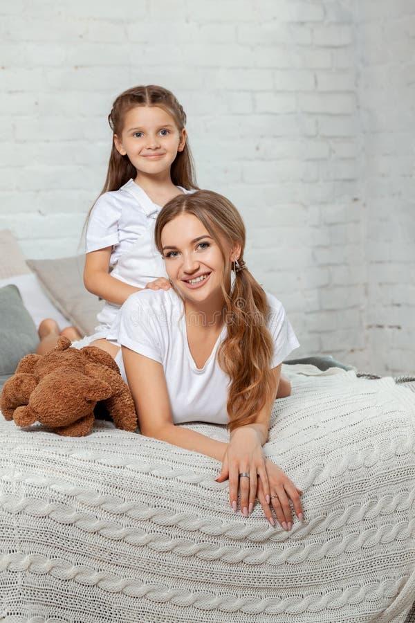 Retrato interior de una madre hermosa con ella pequeña hija encantadora que presenta contra interior del dormitorio imagen de archivo