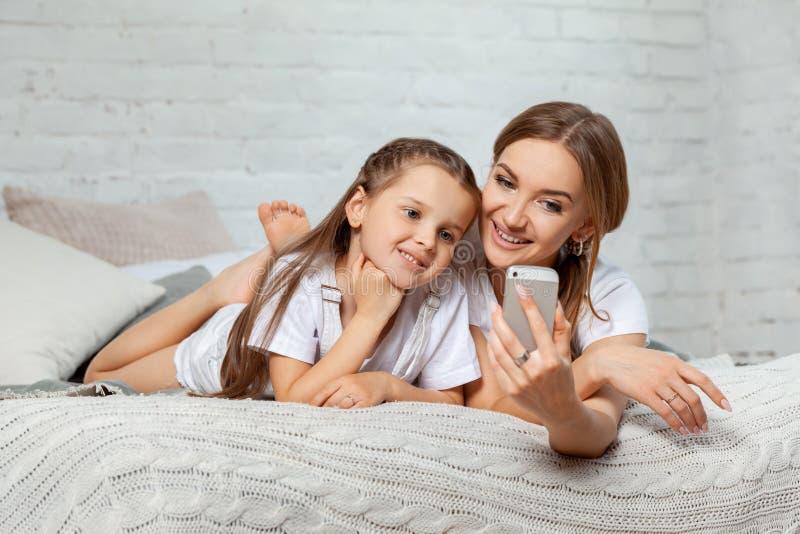 Retrato interior de una madre hermosa con ella pequeña hija encantadora que presenta contra interior del dormitorio foto de archivo