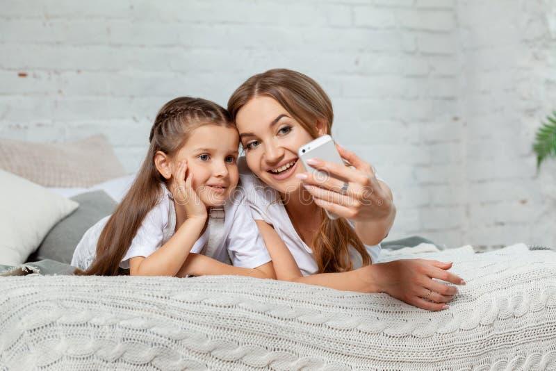 Retrato interior de una madre hermosa con ella pequeña hija encantadora que presenta contra interior del dormitorio imagenes de archivo