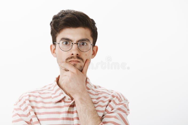 Retrato interior del empollón masculino enfocado serio en vidrios redondos de moda, barbilla de frotamiento con la mano y mirar f fotografía de archivo libre de regalías