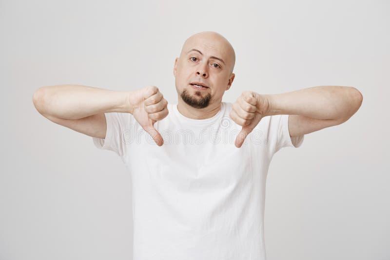 Retrato interior del hombre caucásico calvo molestado infeliz con la barba que muestra los pulgares abajo y que es poco impresion fotografía de archivo