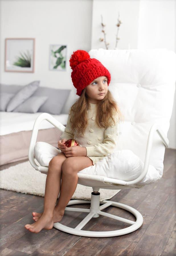 Retrato interior del invierno de una niña en ropa acogedora caliente: el sombrero hecho punto rojo y el blanco del invierno kintt imagen de archivo