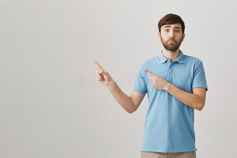 Retrato interior del modelo masculino caucásico con la sonrisa melancólica que siente triste mientras que señala izquierdo, situa fotos de archivo libres de regalías