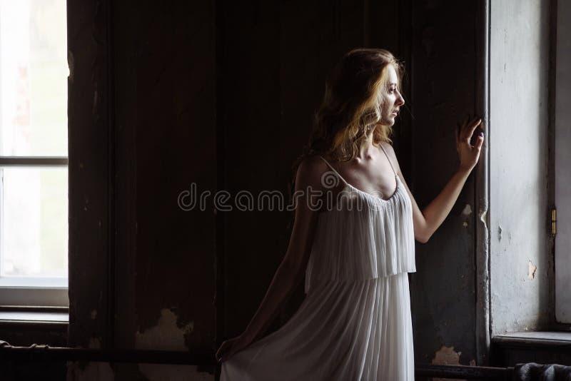 Retrato interior del verano de la muchacha bastante linda de los jóvenes Mujer hermosa que presenta al lado de dos ventanas dentr imagen de archivo libre de regalías