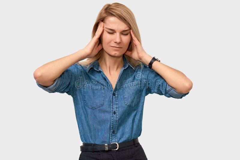 Retrato interno da fêmea nova esgotada que toca em sua cabeça com os olhos fechados que levantam no fundo branco do estúdio Mulhe fotos de stock