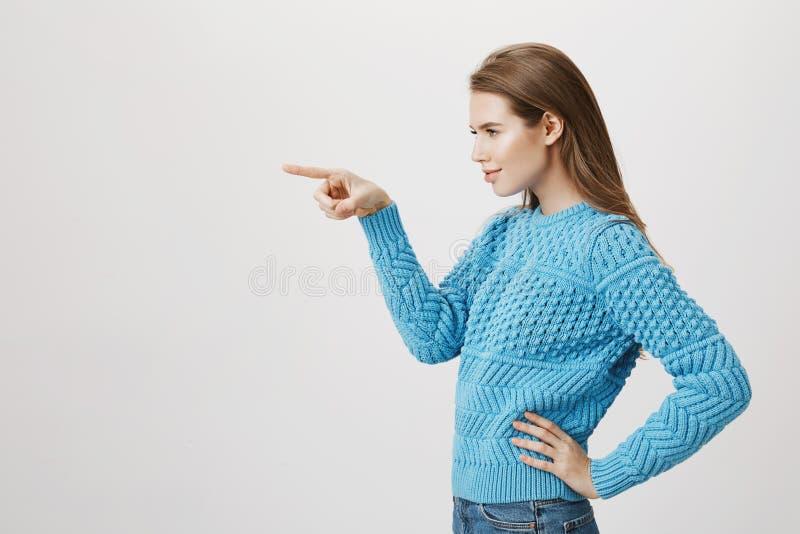 Retrato interno da menina loura bonita que está no perfil com mão na cintura, apontando à esquerda e olhando aquela imagem de stock
