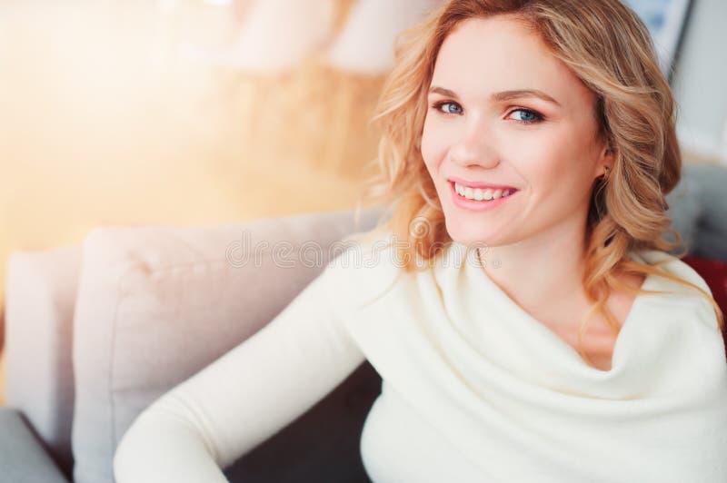 retrato interno da mulher bonita egoísta nova que aprecia o tempo em casa, sentando-se no sofá acolhedor na camiseta morna fotos de stock royalty free