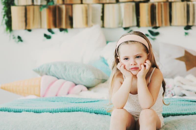 retrato interno de 5 anos bonitos tristes da menina idosa da criança que senta-se na cama foto de stock