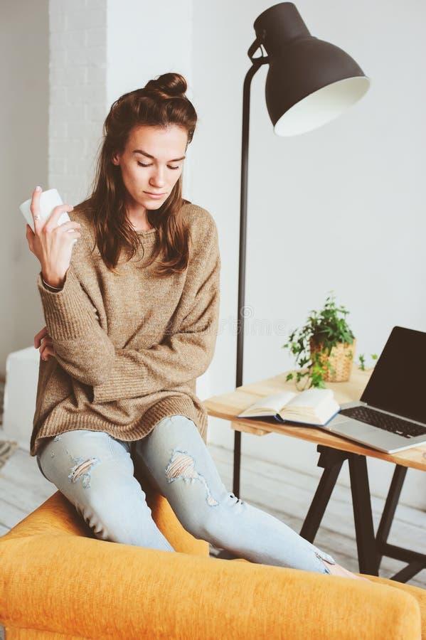 Retrato interno de jovens mulheres pensativas femininos bonitas apenas na sala com o copo do chá ou do café imagem de stock