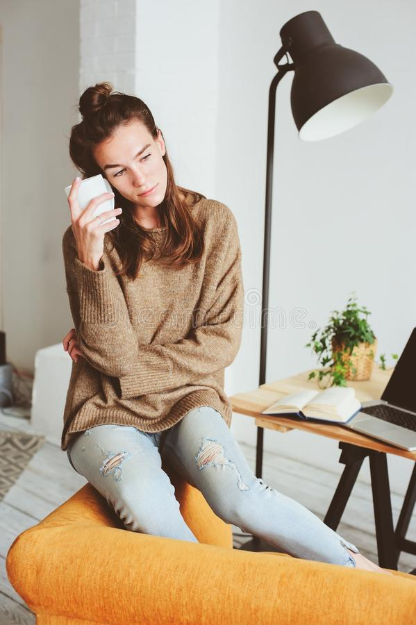 Retrato interno de jovens mulheres pensativas femininos bonitas apenas na sala com o copo do chá ou do café fotos de stock