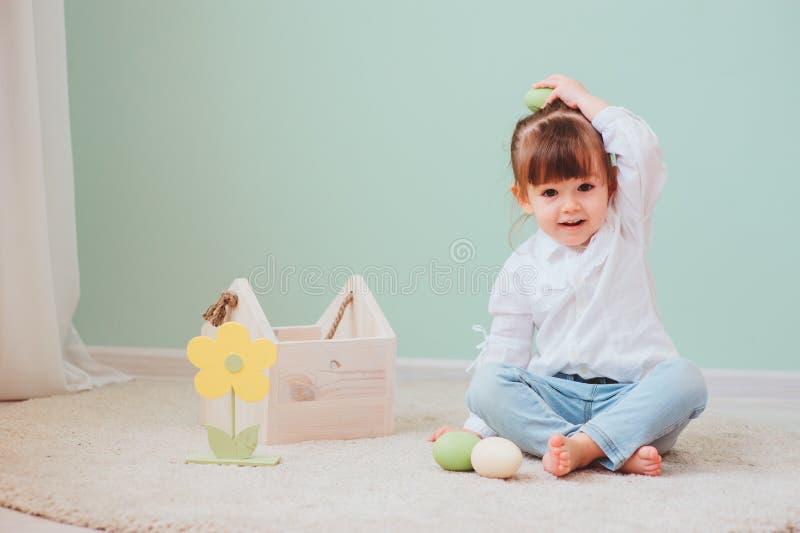 Retrato interno do bebê feliz bonito que joga com decorações de easter fotos de stock