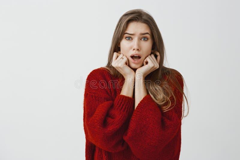 Retrato interno do colega de trabalho fêmea europeu preocupado do timit na camiseta fraca vermelha, guardando as mãos no queixo e fotografia de stock