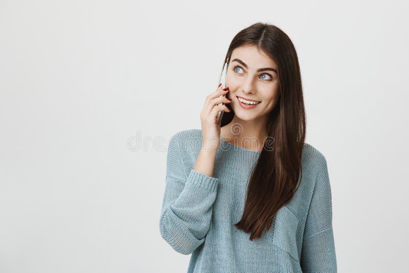 Retrato interno do dentista fêmea novo bonito, falando a seu colega através do telefone celular e olhando de lado, estando no bom imagem de stock royalty free