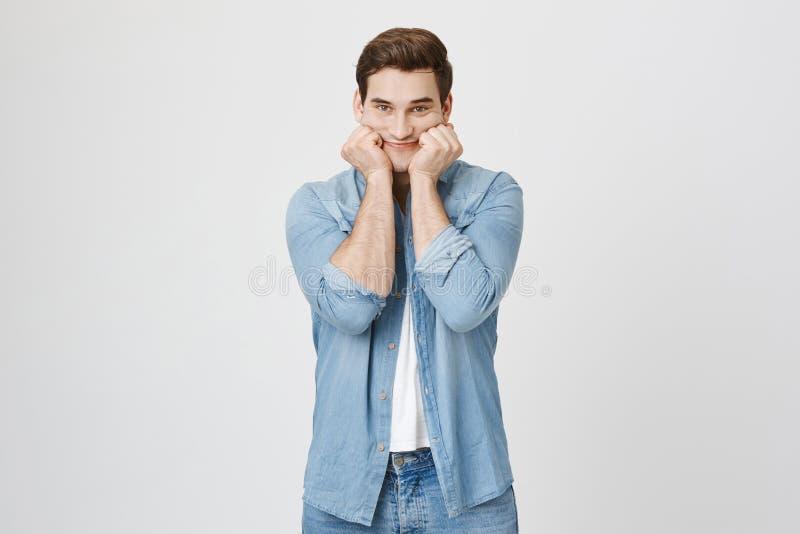 Retrato interno do empregado novo considerável, esticando sua boca com mãos para mostrar o sorriso falsificado ao olhar a câmera fotos de stock