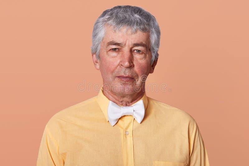 Retrato interno do estúdio do homem sério de cabelo cinzento que olha diretamente na câmera, na camisa amarela vestindo e no bowt fotos de stock