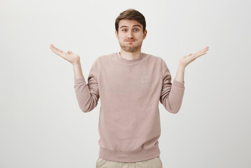 Retrato interno do homem europeu considerável com cerda e mãos de espalhamento do corte de cabelo à moda, mostrando não tiver nen imagem de stock