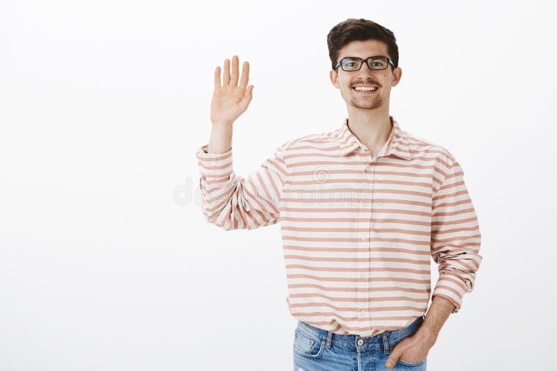 Retrato interno do indivíduo europeu ordinário amigável com barba e do bigode em vidros nerdy, levantando a palma e a ondulação imagens de stock
