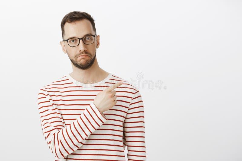 Retrato interno do indivíduo maduro bonito impresso no eyewear, apontando no canto direito superior e fazendo não mau fotos de stock