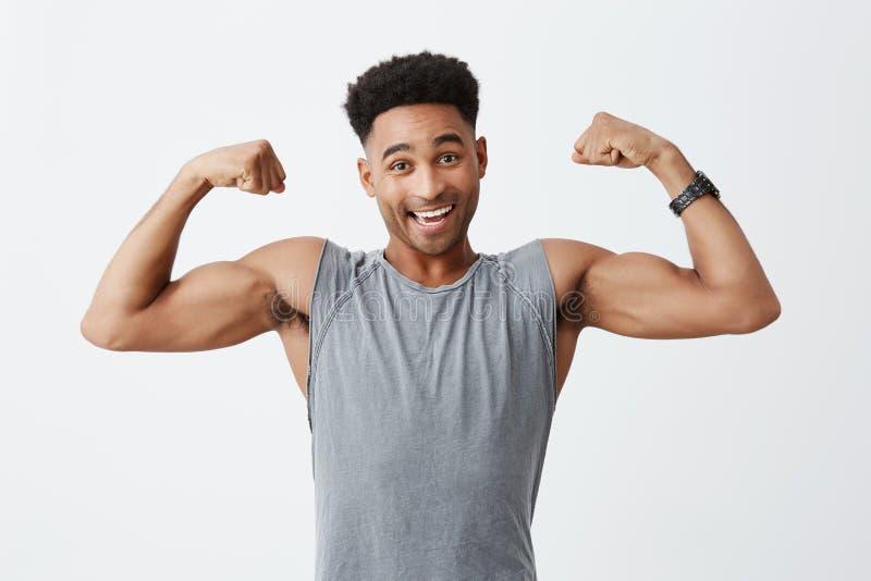 Retrato isolado do homem de pele escura atlético atrativo alegre novo com penteado afro na camisa cinzenta desportiva fotografia de stock royalty free