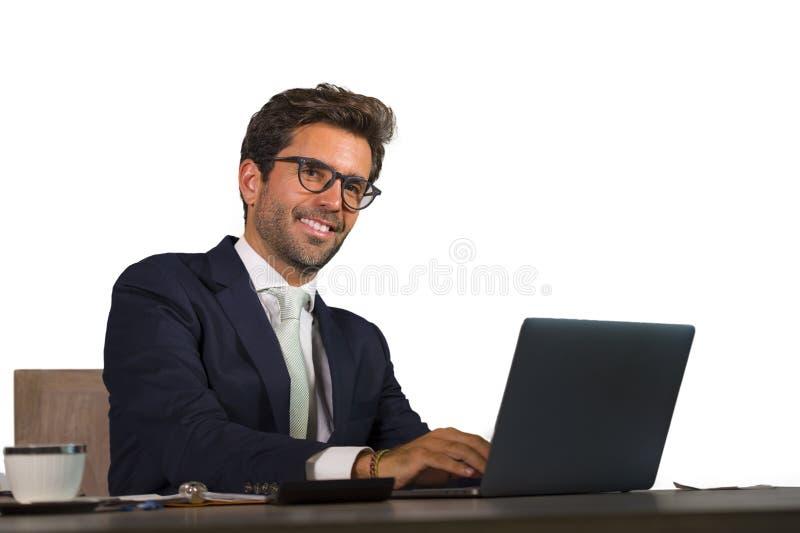 Retrato isolado incorporado da empresa do homem de negócios considerável e atrativo novo que trabalha na mesa co de sorriso do la imagens de stock