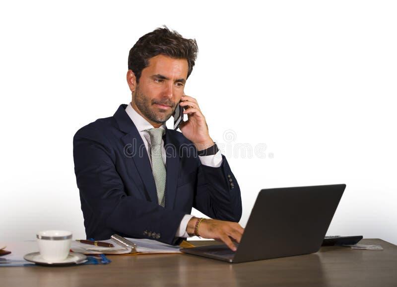 Retrato isolado incorporado da empresa do homem de negócios considerável e atrativo novo que trabalha na mesa de escritório que f imagem de stock royalty free