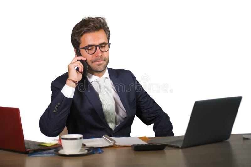 Retrato isolado incorporado da empresa do homem de negócios considerável e atrativo novo que trabalha na mesa de escritório que f imagem de stock